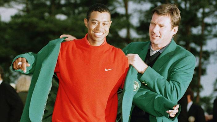 Nick Faldo helps Tiger Woods put on the green jacket following Woods' victory at the 1997 Masters.