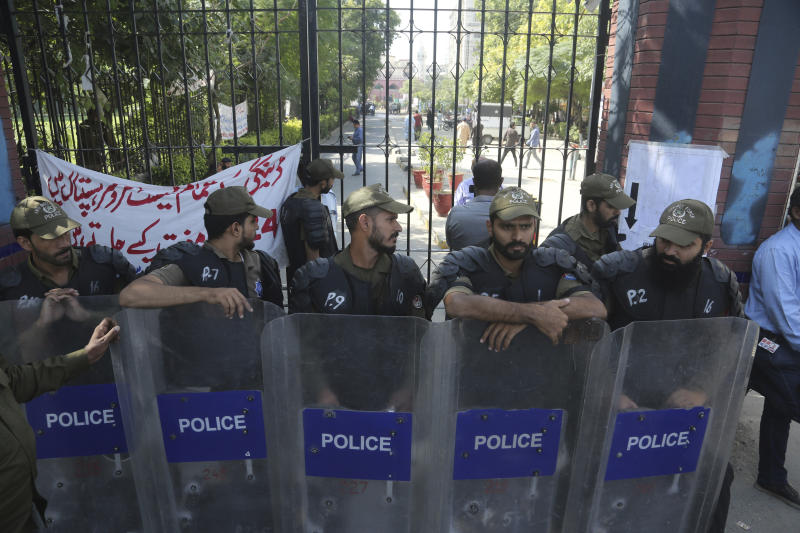 Police officers stand alert outside a hospital where Pakistan former Prime Minister Nawaz Sharif admitted in Lahore, Pakistan, Tuesday, Oct. 22, 2019. Sharif, who was convicted on corruption charges, has been rushed to hospital from the prison after recent blood tests raised doctors' concerns. (AP Photo/K.M. Chaudary)