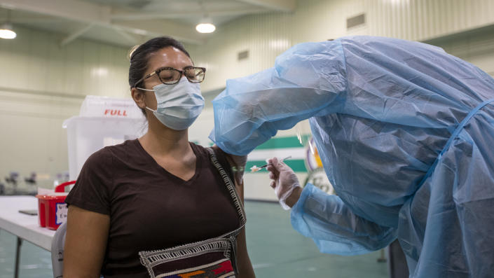 A health worker wearing rubber gloves and full coveralls gives a shot into the upper arm of a seated woman who is wearing a face mask and has her eyes closed.