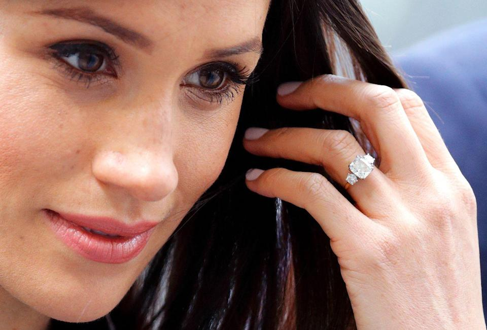 "<p>Prince Harry proposed to the <em>Suits </em>actress with a three-stone diamond ring set on a gold band. The ring, made by royal jeweler Cleave and Company, features a center stone from Botswana flanked by two smaller round diamonds from <a href=""https://www.brides.com/story/meghan-markle-engagement-ring"" rel=""nofollow noopener"" target=""_blank"" data-ylk=""slk:Princess Diana's personal jewelry collection"" class=""link rapid-noclick-resp"">Princess Diana's personal jewelry collection</a>. </p>"
