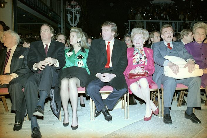 Donald Trump, center, sits with hands folded at the Trump Taj Mahal in Atlantic City, N.J., April 6, 1990, before the start of grand opening ceremonies. Trump attended the gala with his parents, Mary and Fred, and sister US District Court Judge Maryanne Trump Barry, right, and brother Robert Trump, left, and his wife Blaine Trump, third from left wearing green. Trump was dateless. (AP Photo/Charles Rex Arbogast)