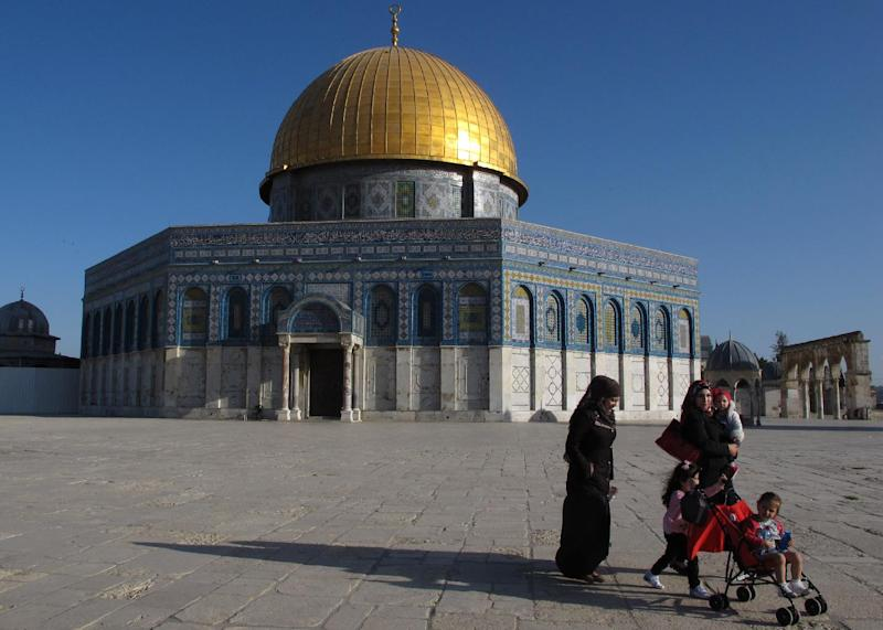 In this Wednesday, April 25, 2012 photo a Palestinian family walks past the Dome of the Rock Mosque in the Al Aqsa Mosque compound in Jerusalem's Old City. After decades of shying away from an ancient pilgrimage route, Muslims are visiting Jerusalem to pray at Islam's third-holiest site and walking straight into a clash between religious clerics, who say such visits are forbidden, and Palestinian leaders urging them to come. (AP Photo/Diaa Hadid)