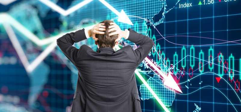 Man in suit holds his head while looking at plunging line graphs.