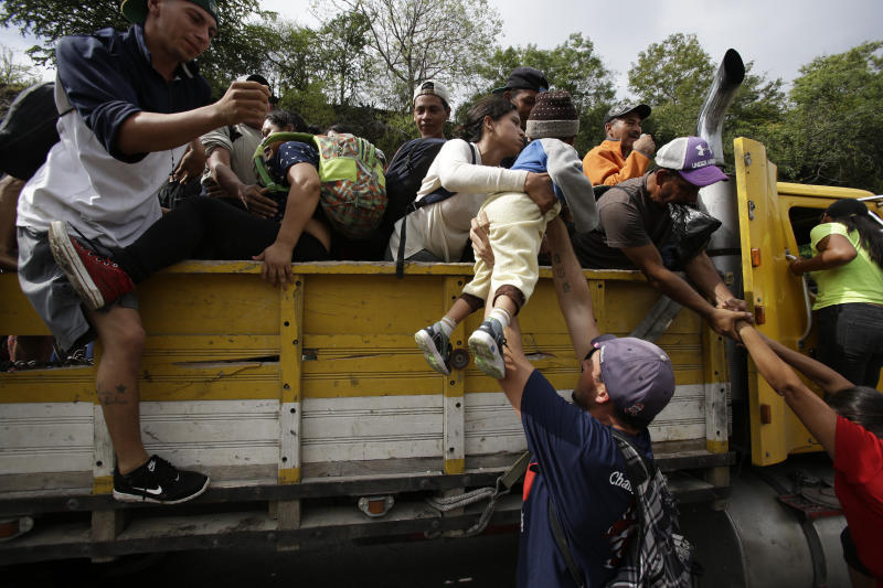 Honduran migrants bound to the U.S border climb into the bed of a truck in Zacapa, Guatemala, Wednesday, Oct. 17, 2018. The group of some 2,000 Honduran migrants hit the road in Guatemala again Wednesday, hoping to reach the United States despite President Donald Trump's threat to cut off aid to Central American countries that don't stop them. (AP Photo/Moises Castillo)