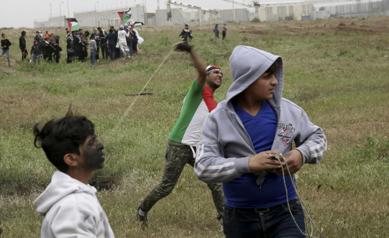 A protester hurls stones near the fence of the Gaza Strip border with Israel, marking first anniversary of Gaza border protests east of Gaza City, Saturday, March 30, 2019. Tens of thousands of Palestinians on Saturday gathered at rallying points near the Israeli border to mark the first anniversary of weekly protests in the Gaza Strip, as Israeli troops fired tear gas and opened fire at small crowds of activists who approached the border fence. (AP Photo/Adel Hana)
