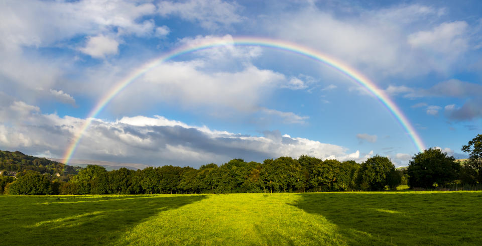 A brightly coloured double rainbow in the English countryside. A stitched image to create a wide angle view.