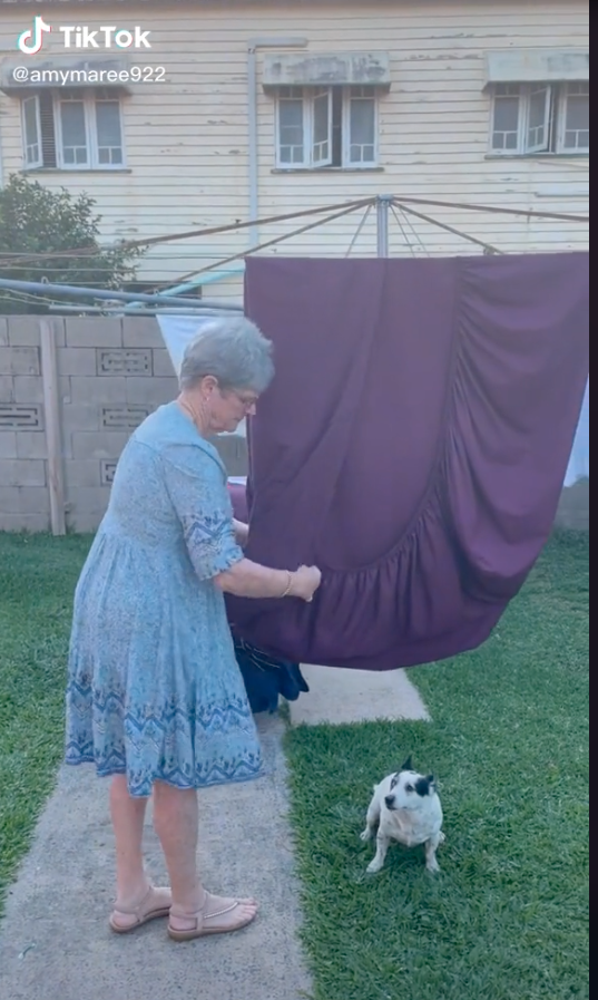 Woman showing how to fold a fitted sheet