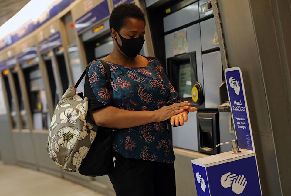 A passenger wearing PPE (personal protective equipment) of a face mask as a precautionary measure against COVID-19, uses a newly installed Hand Sanitser station to clean their hands as they pass through King's Cross St Pancrass TfL (Transport for London) Underground station in central London on May 20, 2020. - Britain's official coronavirus death toll is at least 41,000 with almost 10,000 dead in care homes in England and Wales alone, according to a statistical update released on Tuesday. Some 41,020 deaths where COVID-19 was mentioned on the death certificate were registered across the UK by May 8, according to the Office for National Statistics (ONS). (Photo by ISABEL INFANTES / AFP) (Photo by ISABEL INFANTES/AFP via Getty Images)