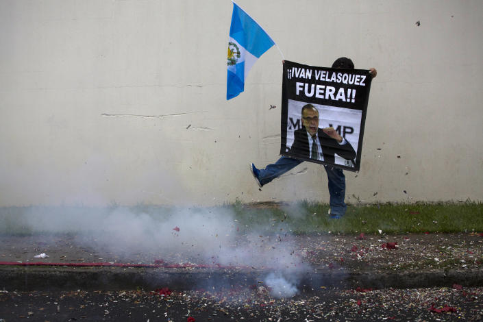 Firecrackers go off as a supporter in favor of a decision by Guatemala's President Jimmy Morales to shut down a U.N.-sponsored anti-graft commission led by Ivan Velasquez, protests outside the United Nations International Commission Against Impunity, CICIG, headquarters in Guatemala City, Friday, Aug. 31, 2018. Last week the Supreme Court allowed a request brought by the CICIG and Guatemalan prosecutors to strip Morales' immunity from prosecution to go to Congress for consideration. (AP Photo/Moises Castillo)