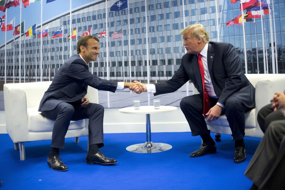 FILE - In this July 11, 2018 file photo, U.S. President Donald Trump and French President Emmanuel Macron shake hands during their bilateral meeting in Brussels, Belgium. EU foreign policy is widely expected to change to meet anticipated future bruising, confrontational challenges. (AP Photo/Pablo Martinez Monsivais, File)