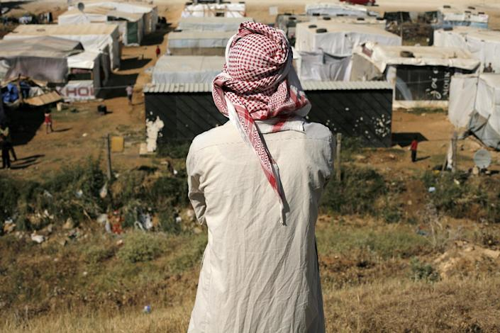 A handout picture released by Caritas Internationalis shows a man looking at a Syrian refugee camp in the Lebanese village of Zahle, on June 17, 2014 (AFP Photo/Matthieu Alexandre)