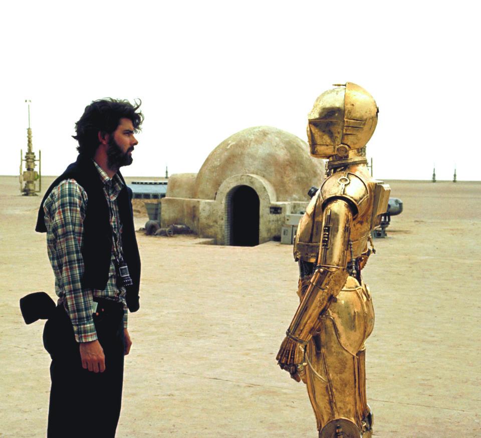 British actor Anthony Daniels (who plays C-3PO) with American director, screenwriter and producer George Lucas on the set of his movie Star Wars: Episode IV - A New Hope. (Photo by Sunset Boulevard/Corbis via Getty Images)
