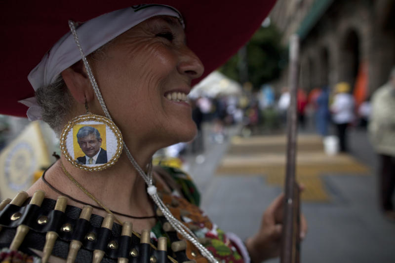 A supporter of Andres Manuel Lopez Obrador, presidential candidate for the Democratic Revolution Party (PRD) wears earrings with his photo before the closing rally of his campaign at the main Zocalo plaza in Mexico City, Wednesday, June 27, 2012. General elections in Mexico are scheduled for Sunday, July 1. (AP Photo/Esteban Felix)