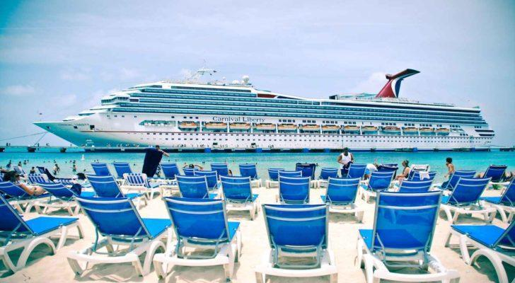 Carnival (CCL) cruise ship on water in front of beach with chairs
