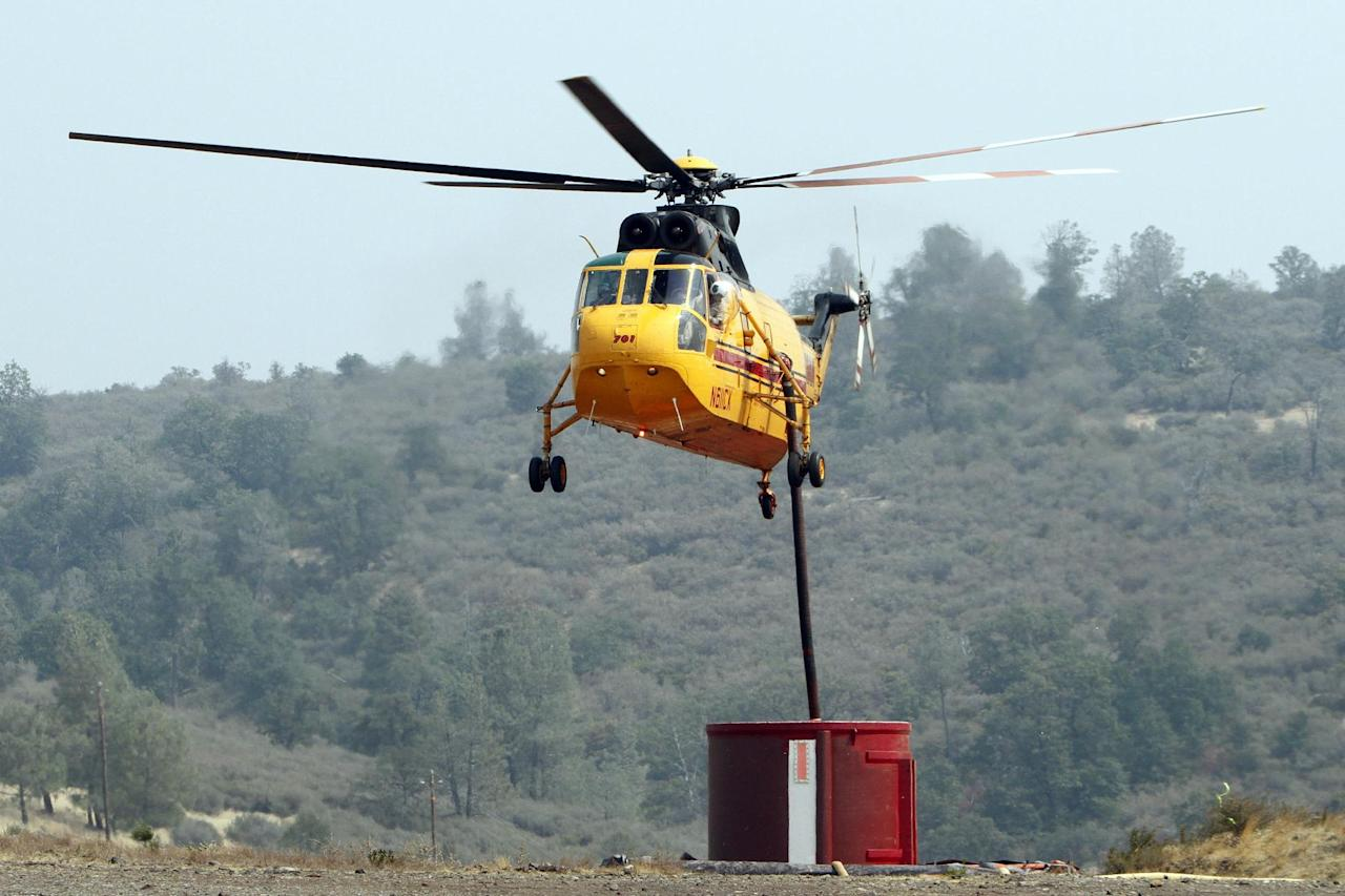 A firefighting helicopter reloads its supply of retardant before heading out to make a drop on the Ponderosa Fire near Paynes Creek, Calif., Wednesday, Aug. 22, 2012. The Ponderosa Fire, which has scorched about 38 square miles since Saturday, was 50 percent contained Wednesday morning, according to the California Department of Forestry and Fire Protection. The threat to homes about 35 miles east of Redding has dropped from 3,500 earlier this week to roughly 200 residences. (AP Photo/Rich Pedroncelli)