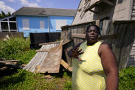In this Sept. 4, 2021, photo, Lationa Kemp, 57, talks with a housing advocate in the aftermath of Hurricane Ida outside her rental home in the Lower Ninth Ward of New Orleans. (AP Photo/Matt Slocum)