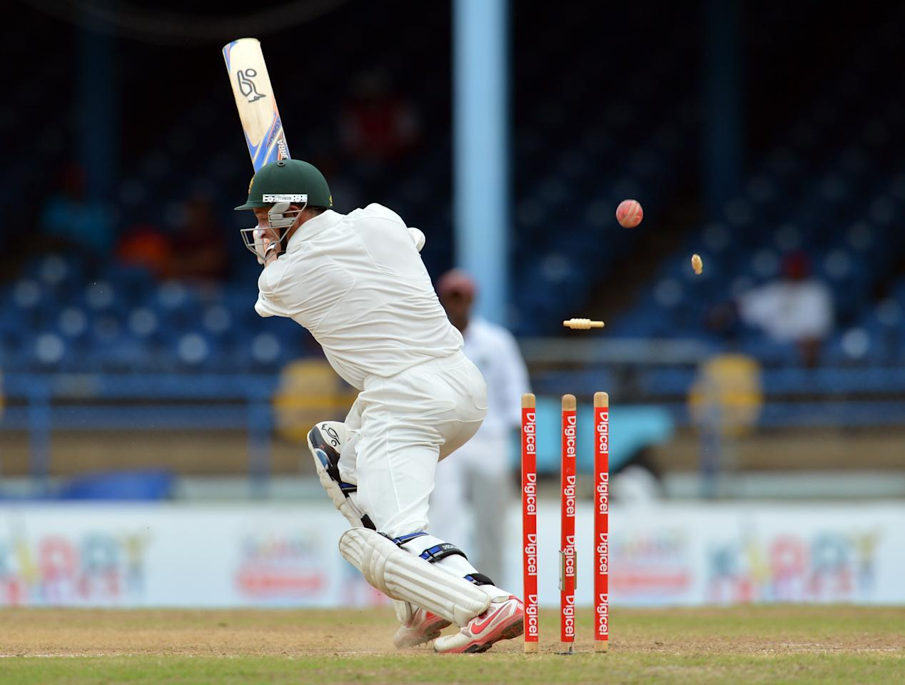 Australian batsman Michael Hussey is bowled out by West Indies Kemar Roach during the final day of the second-of-three Test matches between Australia and West Indies April19, 2012 at Queen's Park Oval in Port of Spain, Trinidad.