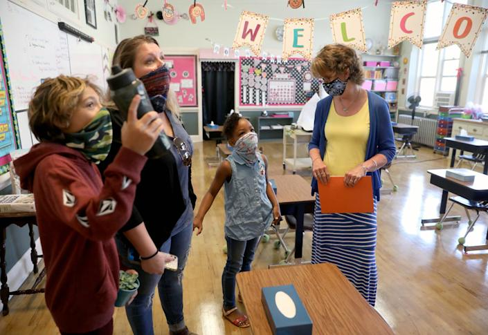 "China Arkansas, 8, center, greets teacher Carol Keane-Stein, far right at Mount Saint Mary's Academy in Grass Valley. Amber Waters, left, and son Jaeden Waters, 10, look at the classroom. <span class=""copyright"">(Gary Coronado/Los Angeles Times)</span>"