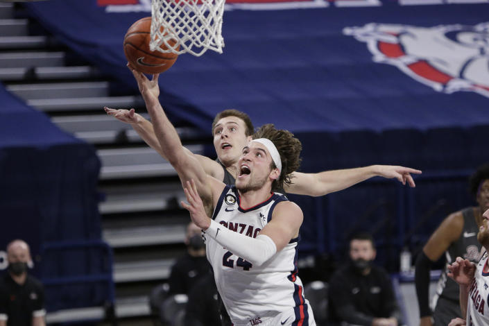 FILE - Gonzaga forward Corey Kispert, front, shoots in front of Santa Clara forward Josip Vrankic during the second half of an NCAA college basketball game in Spokane, Wash., in this Thursday, Feb. 25, 2021, file photo. Kispert has made The Associated Press All-America first team, announced Tuesday, March 16, 2021.(AP Photo/Young Kwak, File)