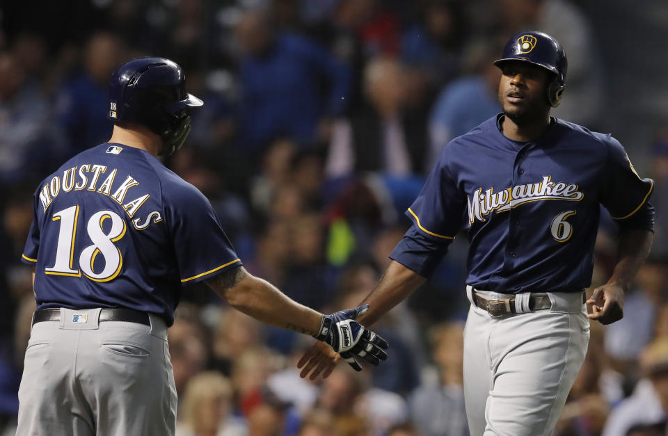 Milwaukee Brewers' Lorenzo Cain, right, celebrates scoring a run against the Chicago Cubs with teammate Mike Moustakas during the first inning of a baseball game Monday, Sept. 10, 2018, in Chicago. (AP Photo/Jim Young)