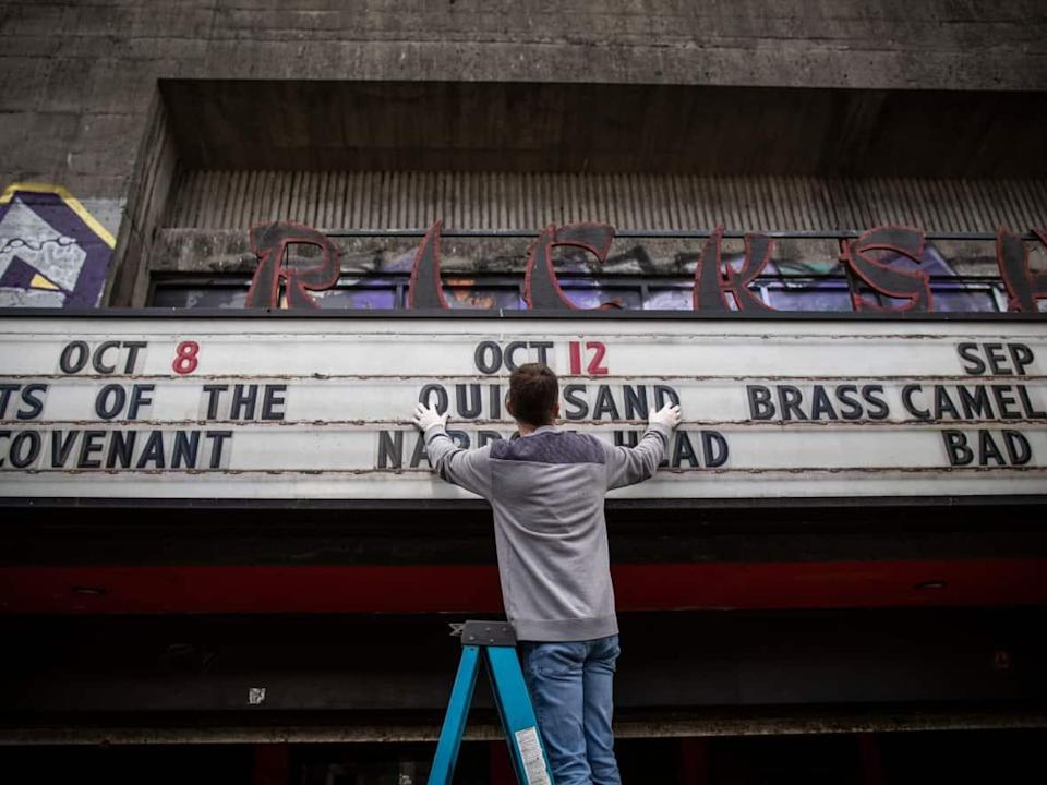 An employee changes the marquee at the Rickshaw Theatre in Vancouver, B.C., on Thursday, Oct. 7, 2021. Like many in the music industry, the owner of the venue, located in the city's Downtown Eastside, has been hit hard by long months of pandemic shut downs and venue restrictions. (Ben Nelms/CBC - image credit)