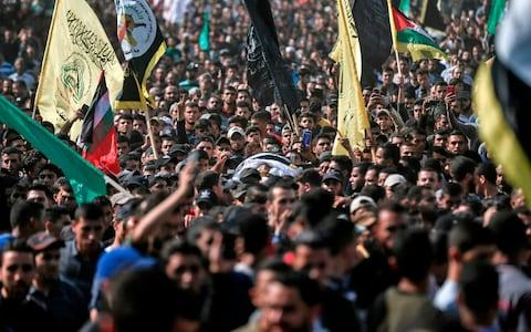 Mourners chant slogans as they carry the body of Palestinian Islamic Jihad senior leader Baha Abu Al-Ata - Credit: Photo by MAHMUD HAMS/AFP via Getty Images