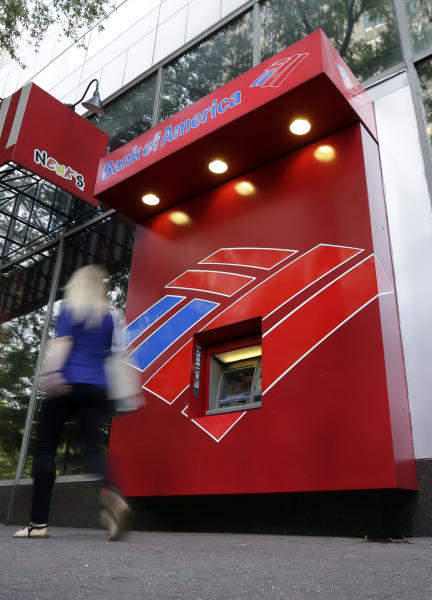 A woman walks past a Bank of America ATM in downtown Charlotte, N.C., Tuesday, July 16, 2013. Bank of America Corp. reports quarterly financial results before the market open on Wednesday, July 17, 2013. (AP Photo/Chuck Burton)