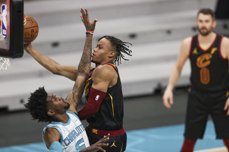 Cleveland Cavaliers guard Darius Garland is fouled by Charlotte Hornets forward Jalen McDaniels (6) as he drives to the basket during the first quarter of an NBA basketball game in Charlotte, N.C., Wednesday, April 14, 2021. (AP Photo/Nell Redmond)