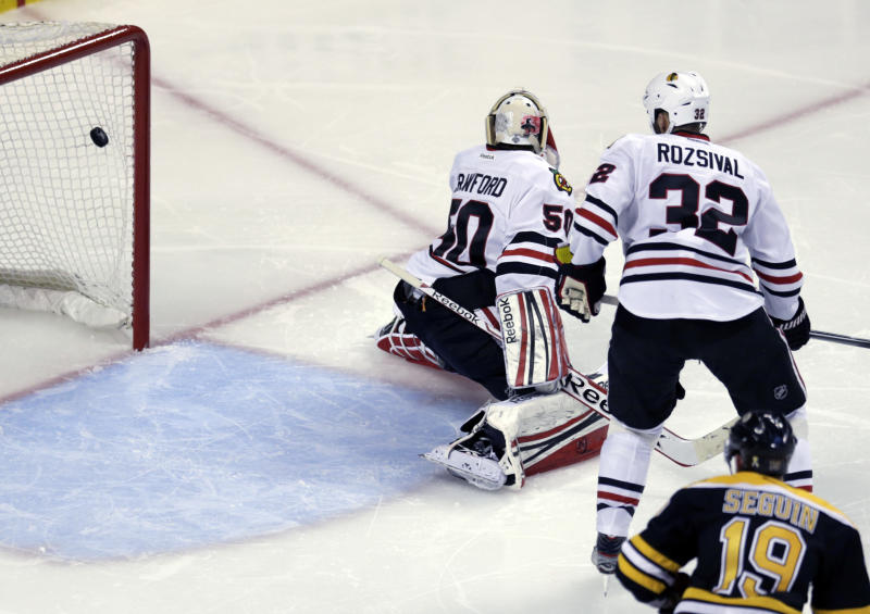 The puck from Boston Bruins' Daniel Paille, not seen, soars into the net past Chicago Blackhawks goalie Corey Crawford (50) and defenseman Michal Rozsival (32), of the Czech Republic, during the second period in Game 3 of the NHL hockey Stanley Cup Finals in Boston, Monday, June 17, 2013. (AP Photo/Charles Krupa)