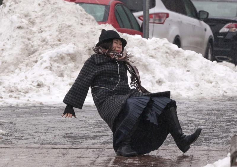 A woman falls while slipping on ice during freezing rain on Roosevelt Island, a borough of Manhattan, in New York January 5, 2014. New York City was hit on Friday by the first severe winter storm of 2014 and was still in the grip of sub-freezing weather on Sunday morning. The woman got up and walked away from the fall. REUTERS/Zoran Milich (UNITED STATES - Tags: SOCIETY ENVIRONMENT TPX IMAGES OF THE DAY)