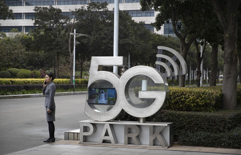 FILE - In this file photo dated Thursday, Dec. 5, 2019, an Huawei employee talks on a cellphone, as she stands next to a sign at Huawei's campus in Shenzhen in southern China's Guandong Province. The European Union unveiled security guidelines for next generation high-speed wireless networks that stop short of calling for a ban on Huawei, in the latest setback for the U.S. campaign against the Chinese tech company, the EU's executive vice president overseeing digital strategy, Margrethe Vestager, said at a press briefing in Brussels, Wednesday Jan. 29, 2020. (AP Photo/Mark Schiefelbein, FILE)
