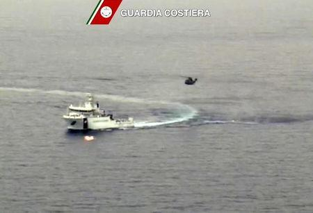 An Italian coast guard vessel is seen with an helicopter during the search and rescue operation underway after a boat carrying migrants capsized overnight, with up to 700 feared dead, in this still image taken from video April 19, 2015. As many as 700 people were feared dead after the fishing boat packed with migrants capsized off the Libyan coast overnight, in what may be one of the worst disasters of the Mediterranean migrant crisis, officials said on Sunday. Twenty-eight people were rescued and 24 bodies recovered from the 20 metre-long vessel, which sank around 70 miles from the Libyan coast, south of the southern Italian island of Lampedusa, the Italian coast guard said. REUTERS/Guardia Costiera/Handout via Reuters TV