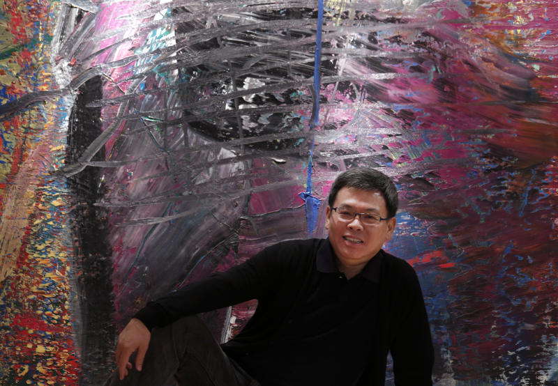 In this photo taken on Monday, April 2, 2012, Indonesian-Chinese farming tycoon Budi Tek poses in front of a painting by Gerhard Richter during an auction preview in Hong Kong. Tek is set to open the De Museum in Shanghai next year featuring Asian and Western contemporary art, after opening his first in Indonesia's capital Jakarta in 2008. While Asia's new generation of wealthy are usually better known for splashing out on extravagant toys such as private jets, mega-sized yachts and supercars some, instead, have built big art collections and now aspire to showcase their refined sensibility to a wider audience.  (AP Photo/Vincent Yu)