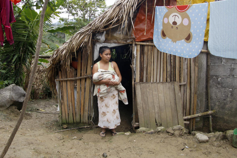 In this Wednesday, Feb. 12, 2014 photo, Irma Lopez, and her son, Sabino Salvador walk in front of her house in San Felipe Jalapa de Diaz, Mexico. Irma's plight garnered national attention last year when a photo showed the 29-year-old woman of Mazatec ethnicity squatting in pain immediately after giving birth in October on the lawn outside the Rural Health Center of the village of San Felipe Jalapa de Diaz. Lopez, and her son, Sabino Salvador, survived with no health problems, but the picture upset many Mexicans when it was widely shared on Twitter and Facebook and shown on the front pages of some national dailies. (AP Photo/Luis Alberto Cruz)