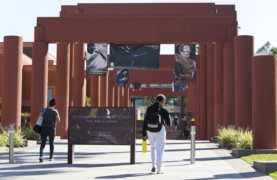 FILE - In this April 25, 2019, photo students walk past the Harriet and Charles Luckman Fine Arts Complex at the Cal State University, Los Angeles campus. The Federal Emergency Management Agency plans to end its mass vaccination pilot programs in Oakland and Cal State LA campus in Los Angeles next month. Officials said Friday, March 26, 2021, that the vaccine sites have provided nearly a half-million doses so far. (AP Photo/Damian Dovarganes, File)