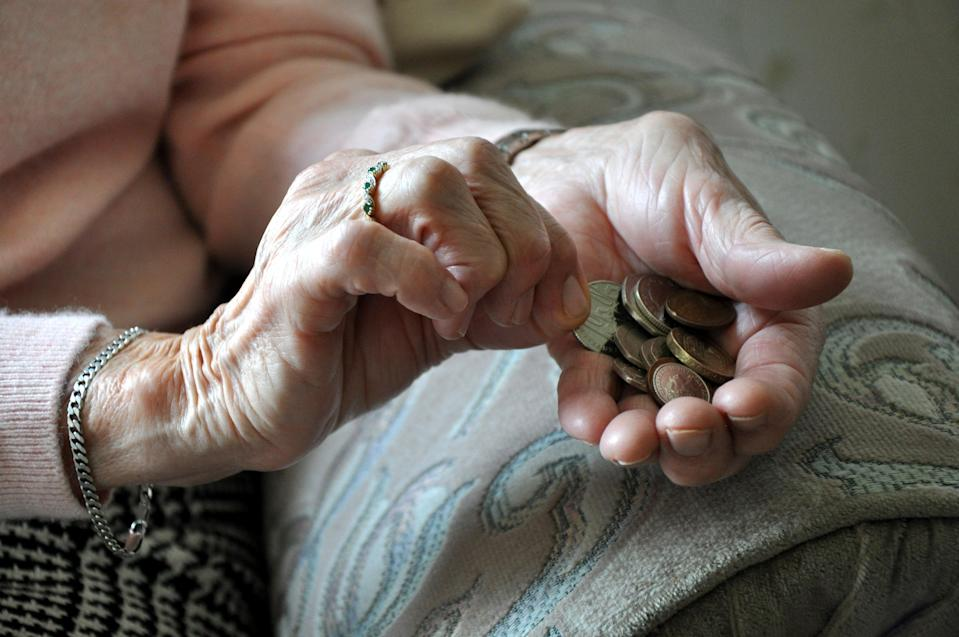 An elderly woman holding coins (PA Archive)