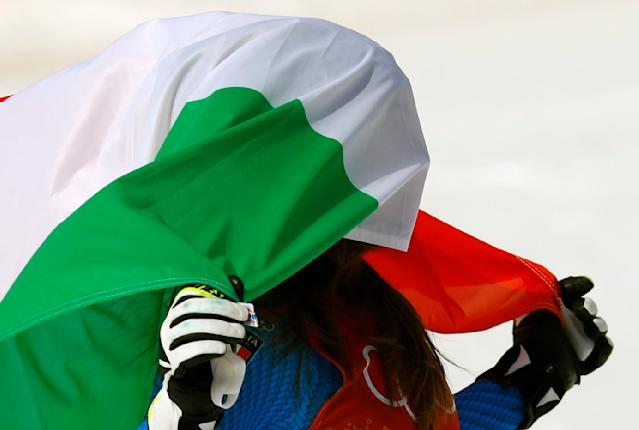 Alpine Skiing - Pyeongchang 2018 Winter Olympics - Women's Downhill - Jeongseon Alpine Centre - Pyeongchang, South Korea - February 21, 2018 - Gold medallist Sofia Goggia of Italy celebrates with the Italian flag during the flower ceremony. REUTERS/Leonhard Foeger