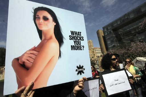 A woman holds up a placard as she takes part in a rally to urge the Lebanese parliament to sign a law against domestic violence, on April 1, 2014, in Beirut