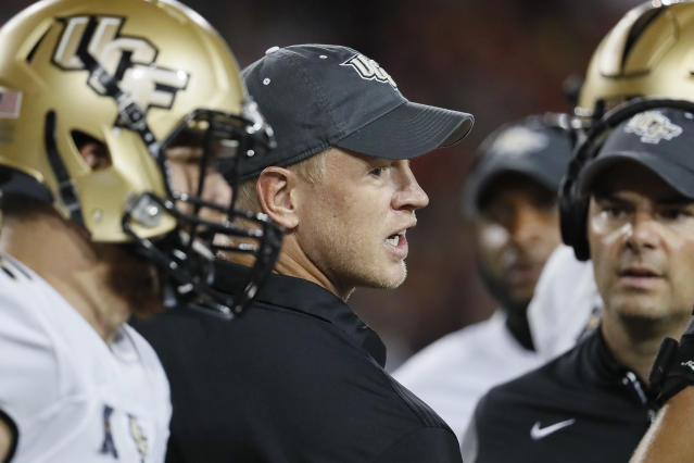 UCF head coach Scott Frost directs his players in a huddle in the first half of an NCAA college football game against Cincinnati, Saturday, Oct. 7, 2017, in Cincinnati. (AP Photo/John Minchillo)