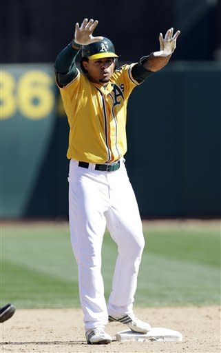 Oakland Athletics' Coco Crisp gestures to his dugout after driving in two-runs with a double against the Texas Rangers during the fourth inning of a baseball game, Wednesday, Oct. 3, 2012, in Oakland, Calif. (AP Photo/Marcio Jose Sanchez)