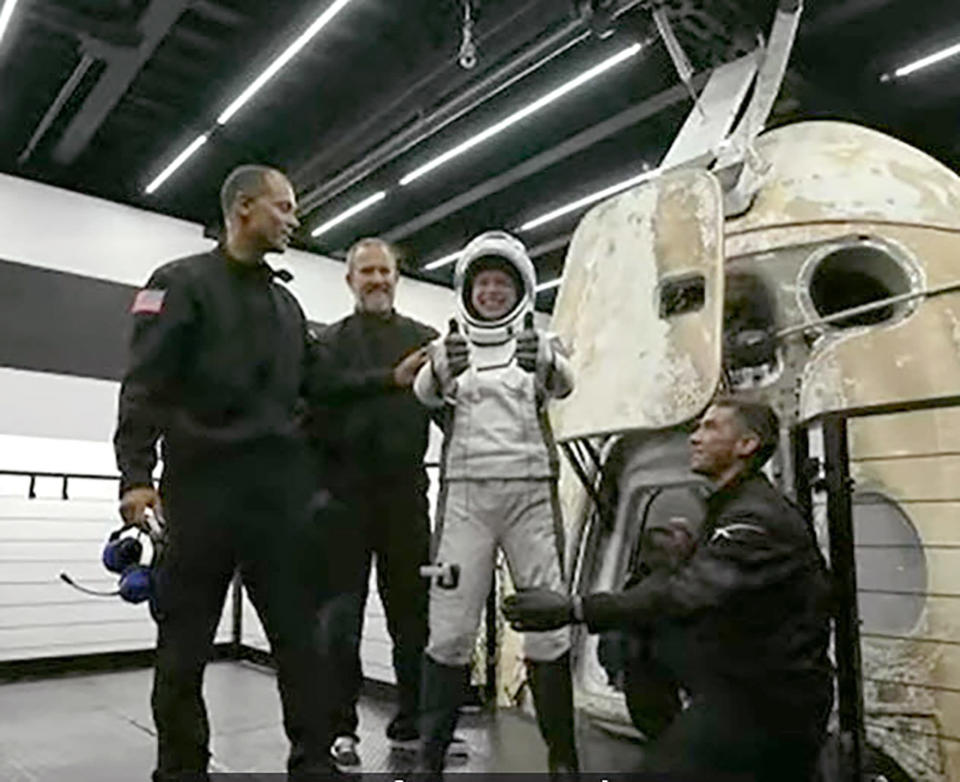 In this image taken from video, Hayley Arceneaux, one of four passengers aboard the SpaceX capsule, reacts after emerging from the capsule Saturday, Sept. 18, 2021, after it was recovered following its splashdown in the Atlantic off the Florida coast. The all-amateur crew was the first to circle the world without a professional astronaut. (Inspiration4 via AP)