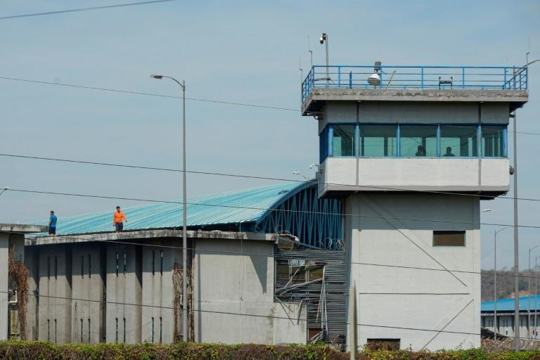 Inmates walk on the roof of a wing of the main regional prison in Guayaquil, Ecuador, where more than 100 prisoners were killed in a clash between inmates (AFP/Fernando Mendez)
