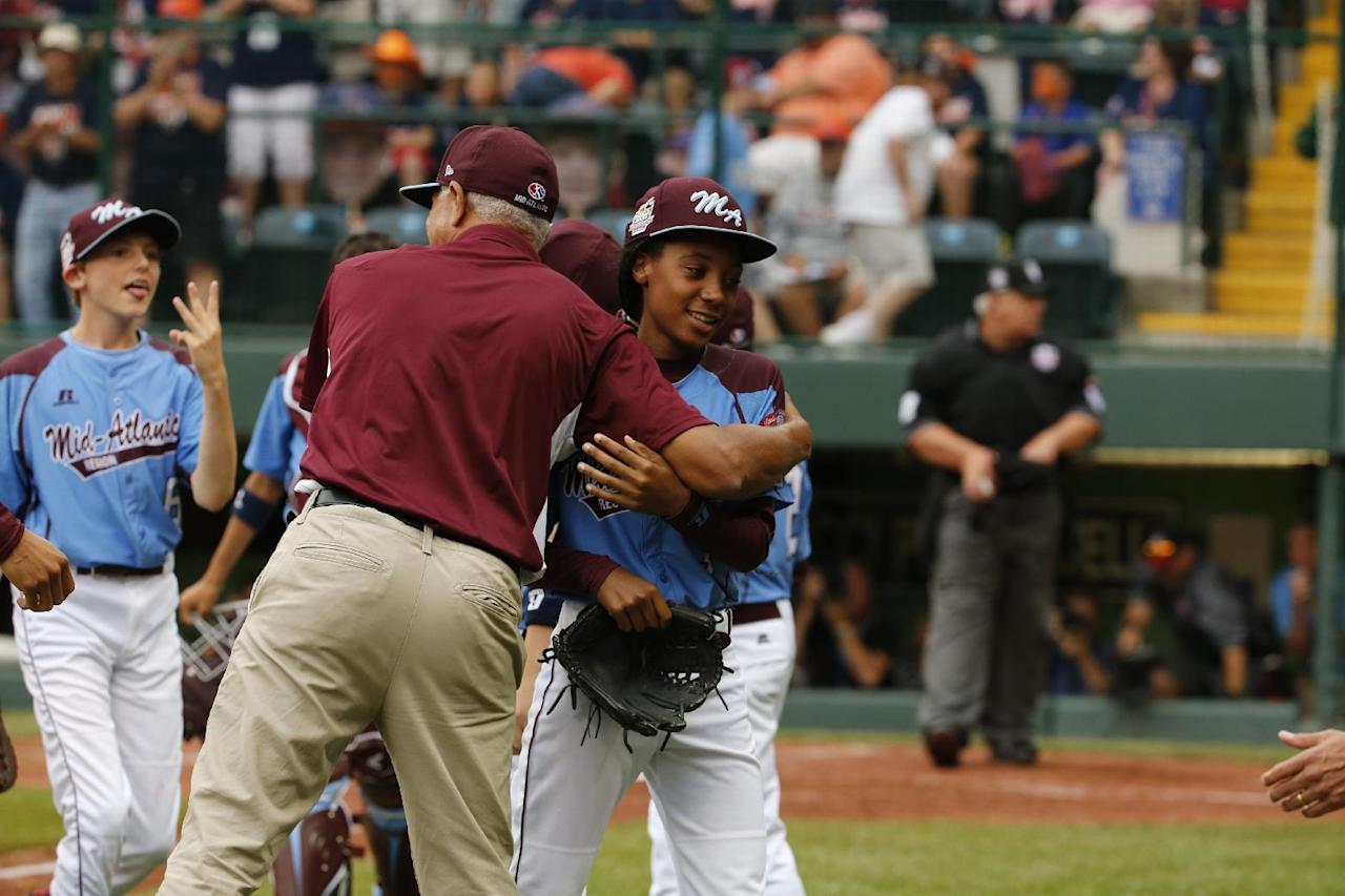 Pennsylvania pitcher Mo'ne Davis, right, celebrates with coach Leland Lott, center, as she returns to the dugout at the end of the fifth inning during a baseball game against Tennessee in United States pool play at the Little League World Series tournament in South Williamsport, Pa., Friday, Aug. 15, 2014. Pennsylvania won 4-0, with Davis pitching a complete game two-hit shutout.(AP Photo/Gene J. Puskar)