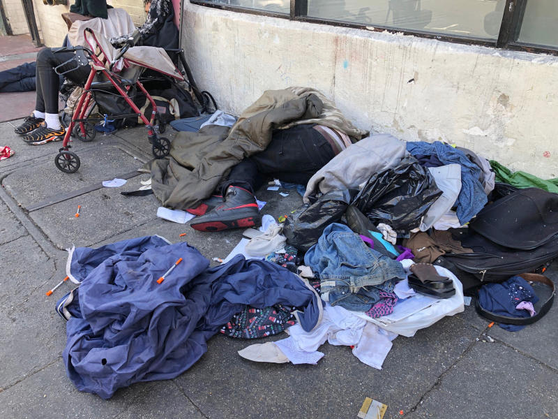 """FILE - In this July 25, 2019, file photo, sleeping people, discarded clothes and used needles are seen on a street in the Tenderloin neighborhood in San Francisco. Seventeen federal law enforcement agencies are teaming up for a year-long crackdown on a notorious area of San Francisco where open drug use has been tolerated for years. U.S. Attorney David Anderson said Wednesday, Aug. 7, 2019, that the federal government is targeting the city's Tenderloin neighborhood with arrests of drug traffickers as the first step in cleaning up a roughly 50-block area he says is """"smothered by lawlessness."""" (AP Photo/Janie Har, File)"""