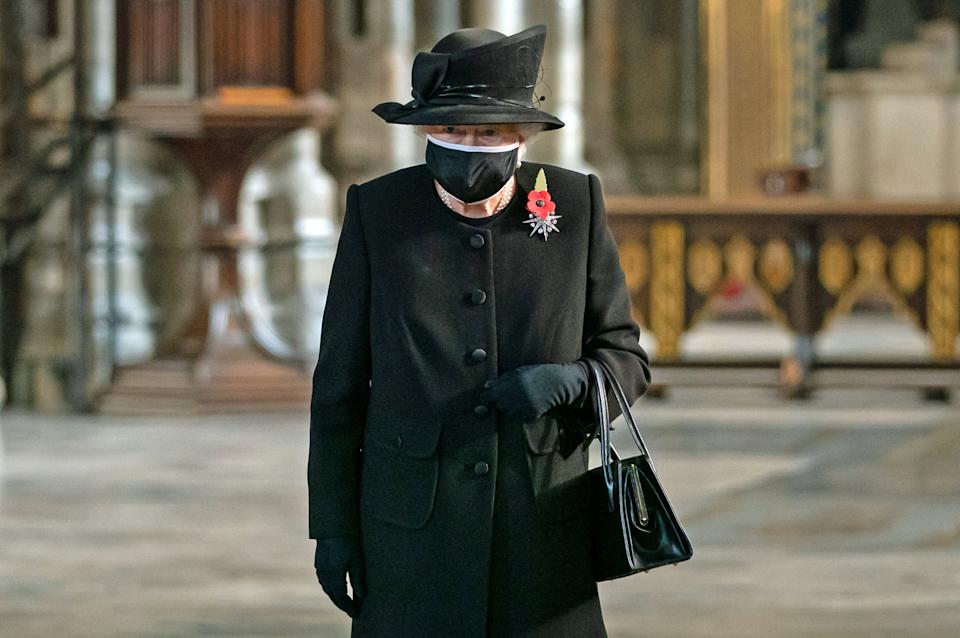 Queen Elizabeth II wearing a black coat, hat and face mask during a ceremony in Westminster Abbey to mark the centenary of the burial of the Unknown Warrior on November 4, 2020