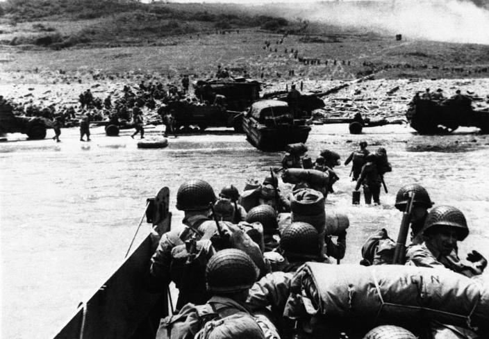 """""""Ducks"""" (amphibious trucks) and a half-track follow foot troops ashore during the invasion of France on a 100-mile front along the Normandy coast by Allied forces on June 6, 1944. (Photo: AP)"""