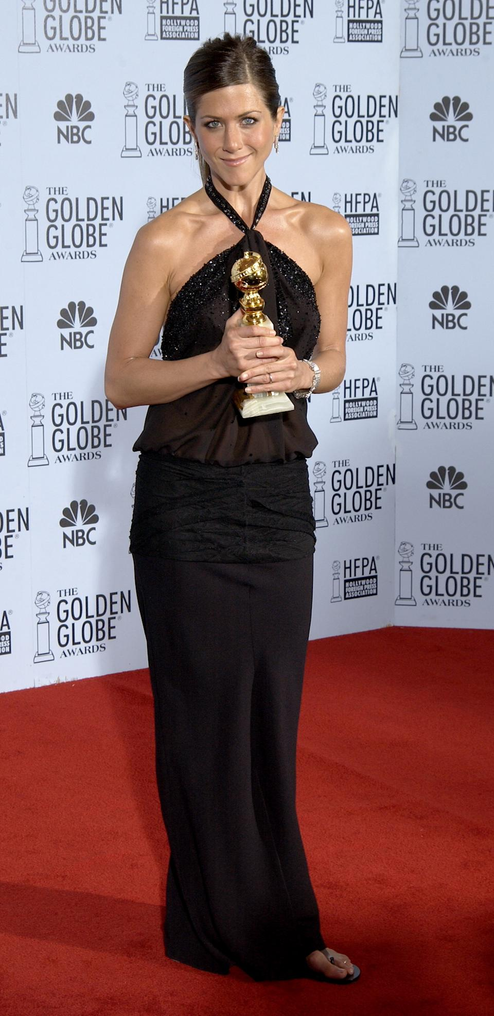 In 2003, Aniston picked up the Golden Globe Award for Best Actress in a Musical or Comedy - and surprised fans by pulling her with her newly darkened locks in a sleek ponytail. (Image via Getty Images)