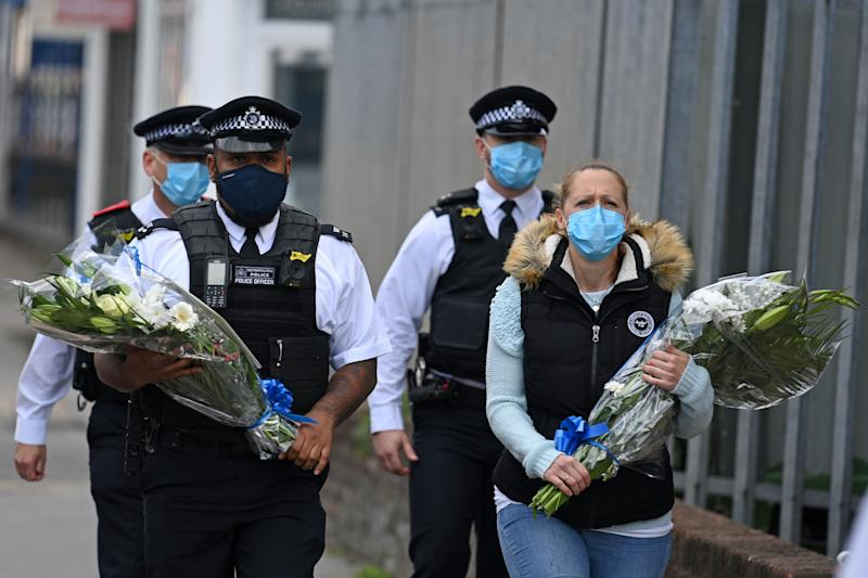 Police officers wearing protective face masks bring floral tributes to the Croydon Custody Centre where the incident took place  (Photo: DANIEL LEAL-OLIVAS via Getty Images)
