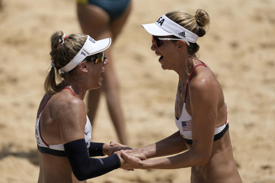 April Ross, left, of the United States, and teammate Alix Klineman celebrate winning a women's beach volleyball Gold Medal match against Australia at the 2020 Summer Olympics, Friday, Aug. 6, 2021, in Tokyo, Japan. (AP Photo/Petros Giannakouris)