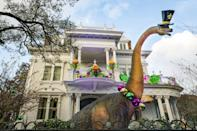 <p>A dinosaur-themed house, this yard is decked out in full Dino Gras decor and it looks like a few very real-looking dinosaurs were in attendance, too! Accents of the traditional Mardi Gras colors purple, green, and gold can be found throughout the scene.</p>